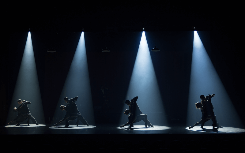 Four couples dancing on stage in spotlights