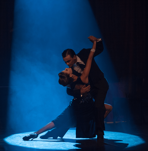 A tango dancer lunges with her partner in spotlight