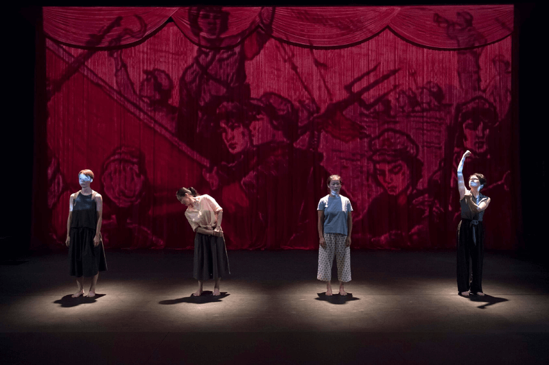 Four women stand in front of cartoon projection in Wen Hui's RED