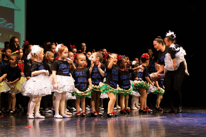 Dance teacher on stage with students at recital