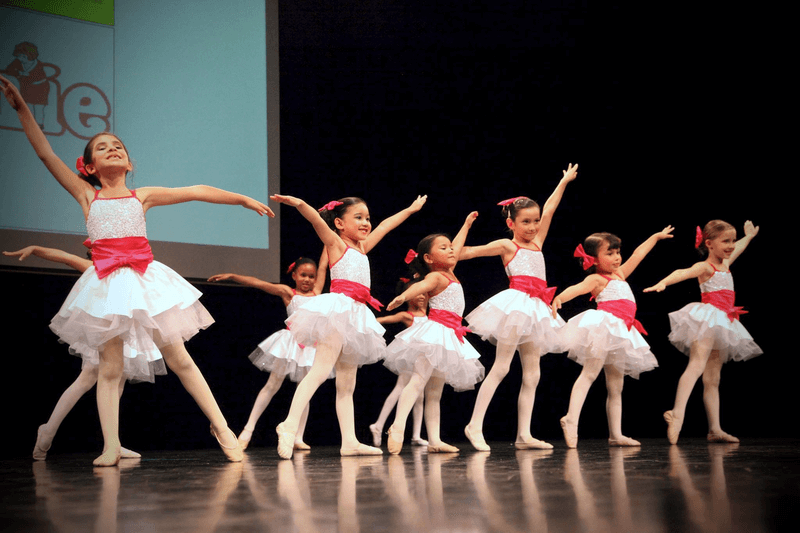 Young ballet students pose on stage