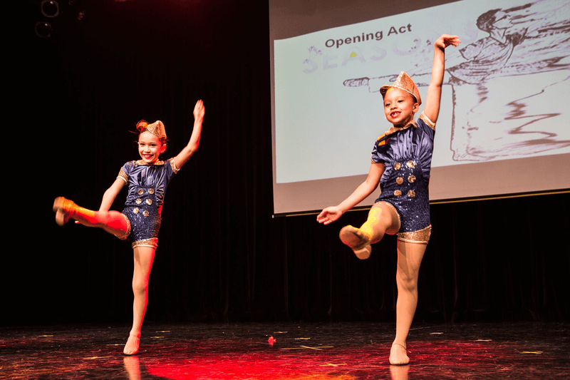 Two young girls dance on stage in jazz routine
