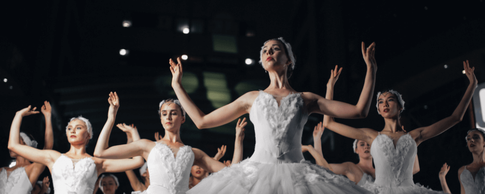 women in white tutus with arms lifted