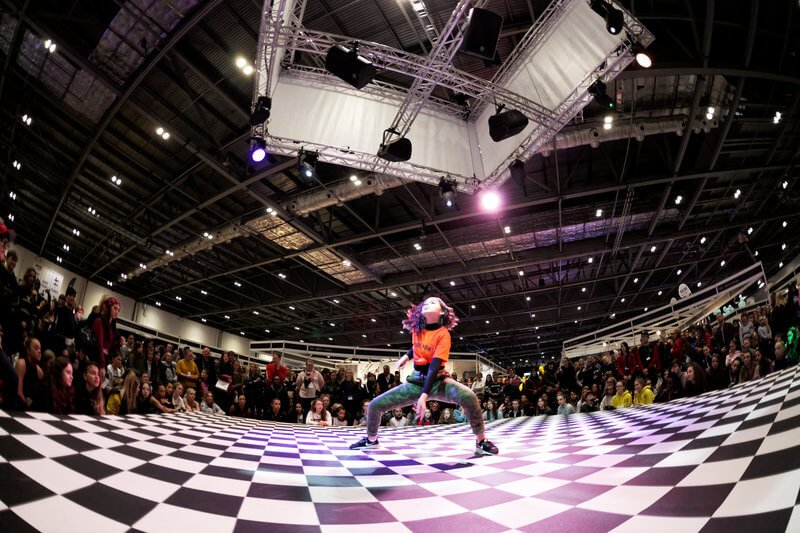 a girl dances on a checkered floor