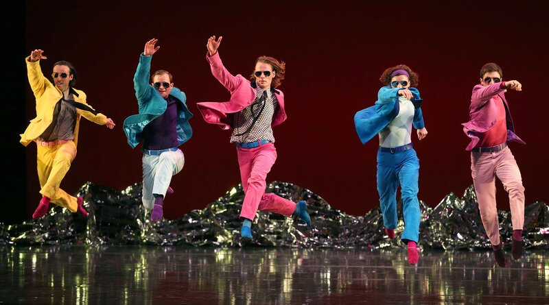 Men run onto stage in colorful suits