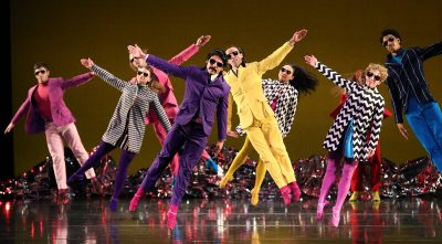 Dancers in sunglasses jump sideways