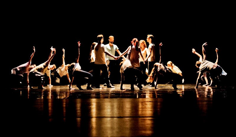 Dancers hold hands, facing each other in a circle