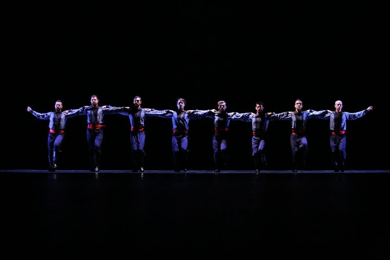 Men link arms and dance in a line