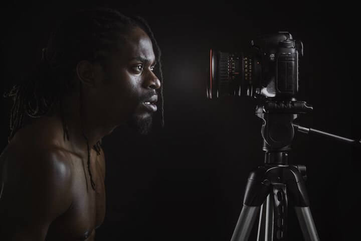 A man looks into a camera on a tripod