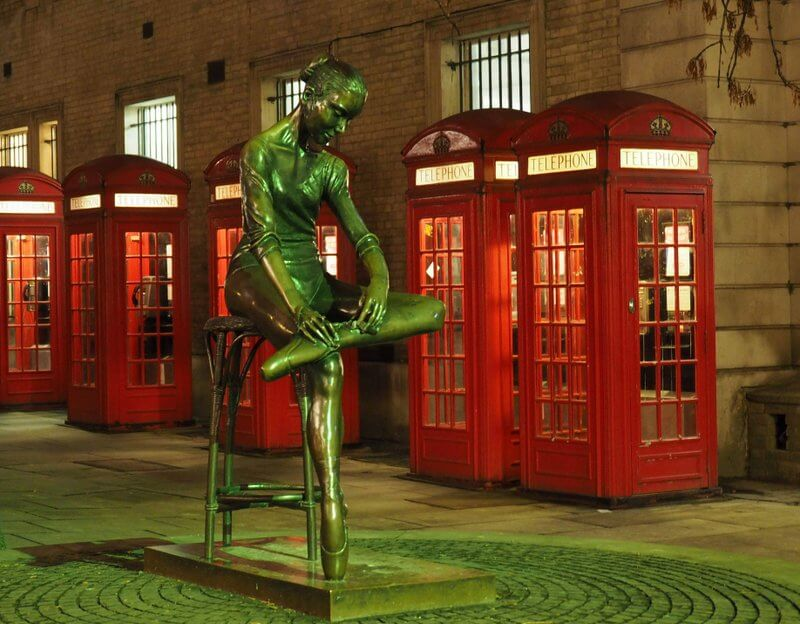 Dance statue in front of red telephone booths