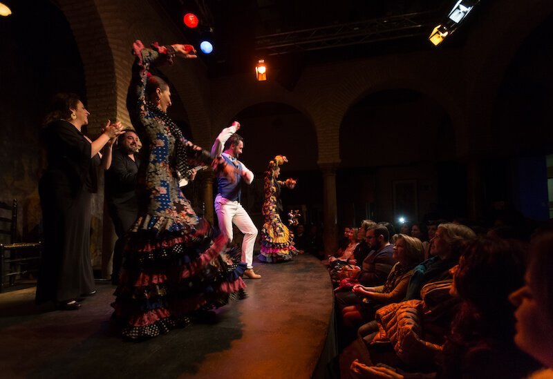 A female flamenco dancer in a ruffled polka dot dress dances with another man and woman at the flamenco museum in Seville, Spain