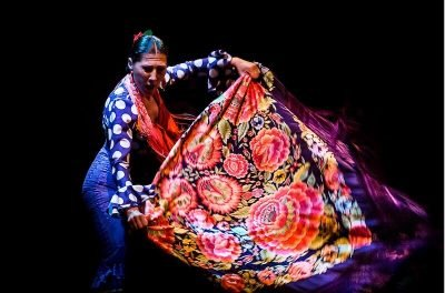 A flamenco dancer in polka dots waves a shawl with red flowers
