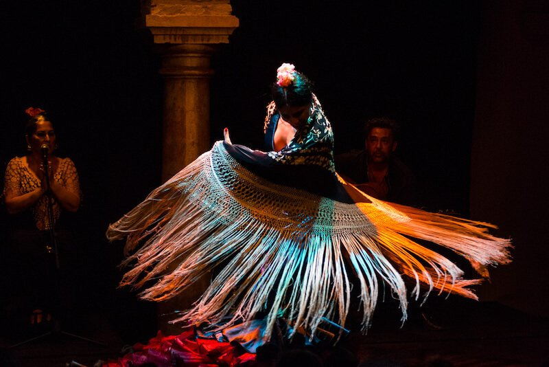 A flamenco dancer with flowers in her hair sweeps a white-fringed shawl