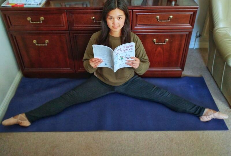 Girl in green sweatshirt stretches and reads ballet book