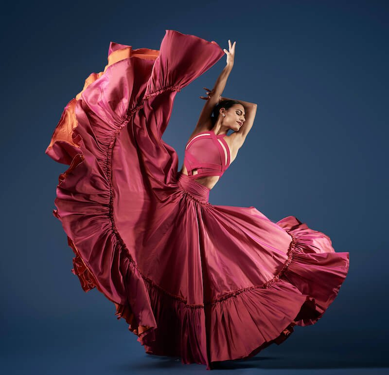 A female dancer flourishes her large pink skirt upwards