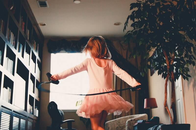 A young girl in pink twirls in her living room