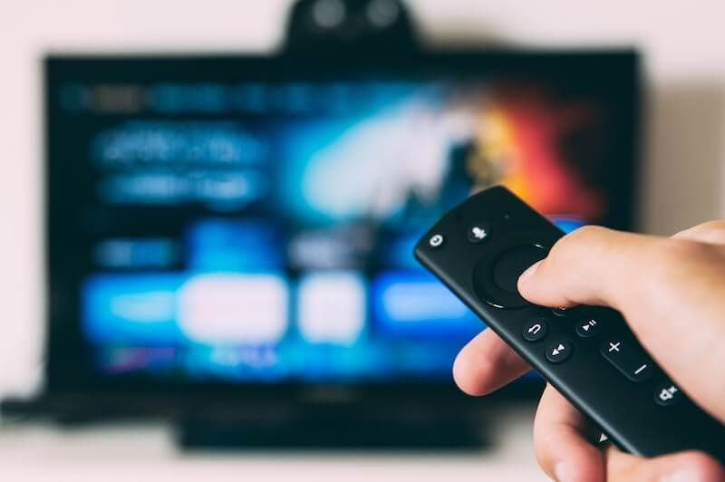 A hand holds a remote in front of a blurry television screen