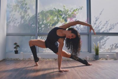 A dancer in black legwarmers stretches in a lunge