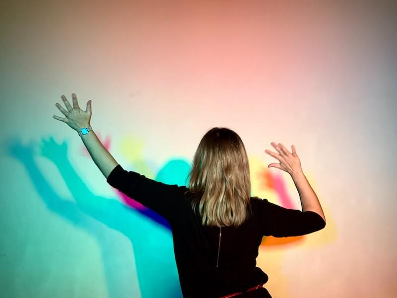 A woman stretches her arms in colored lights