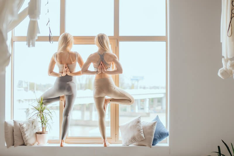 Two women doing yoga in front of window