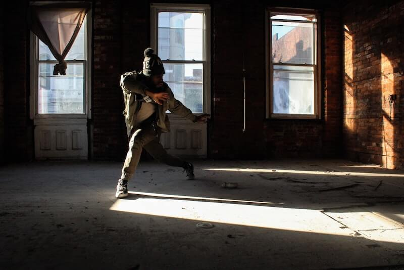 A man in a hat dances indoors while sunlight comes through the window