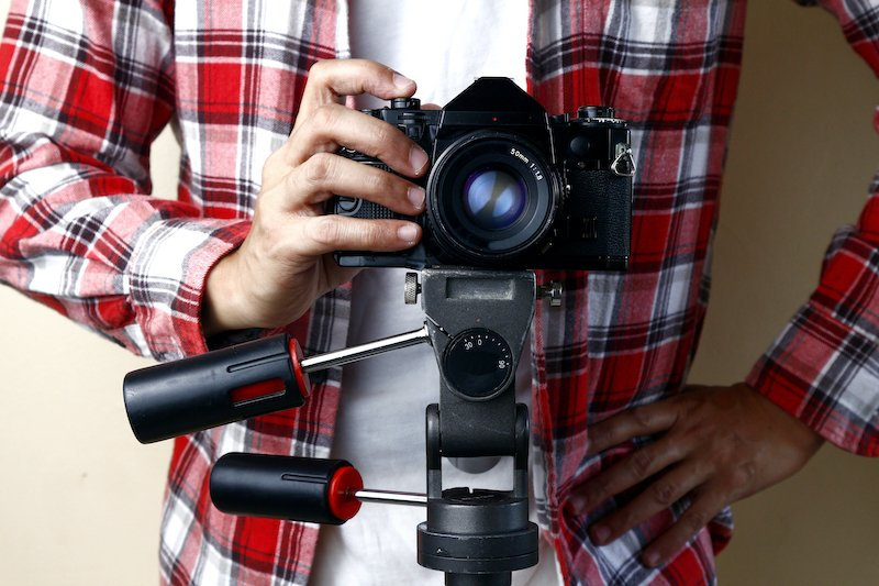 A man in a red and white shirt holds a camera on a tripod