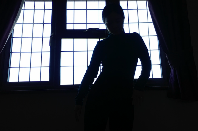 A woman in silhouette against window shifts weight to side
