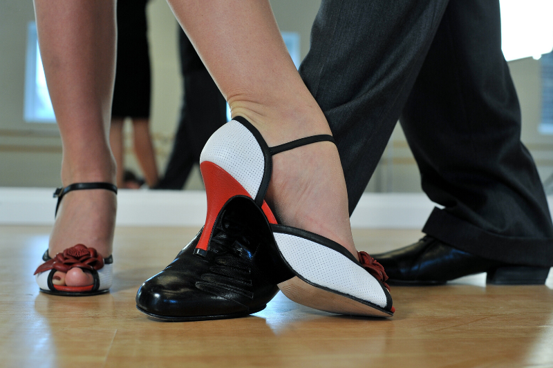 A lady's and a gentleman's pair of ballroom shoes on a wood floor
