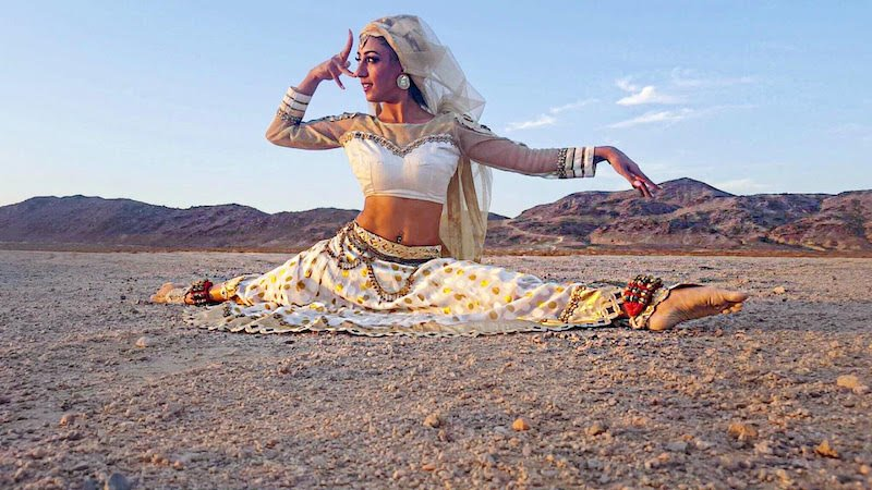 A woman in white Indian dress does the splits on a rocky landscape