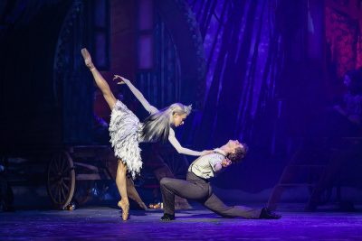 A man lunges back on stage and a ballerina presses a hand to his chest, her leg in back arabesque