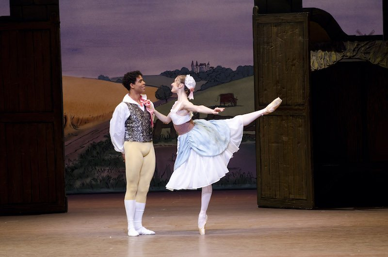 A dancer kicks her leg back into arabesque and touches a man's chest