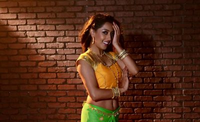 A smiling woman with gold bangles stands in front of a brick wall