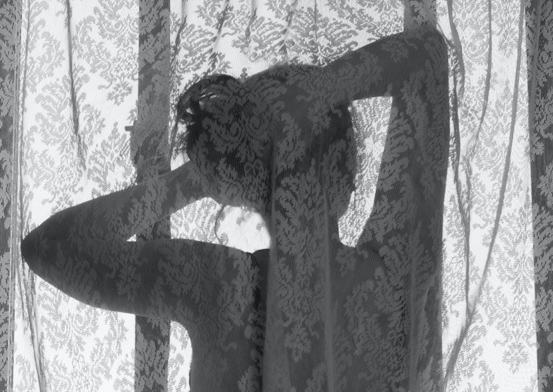 A shadow of a woman with her arms behind her head and a light grey curtain