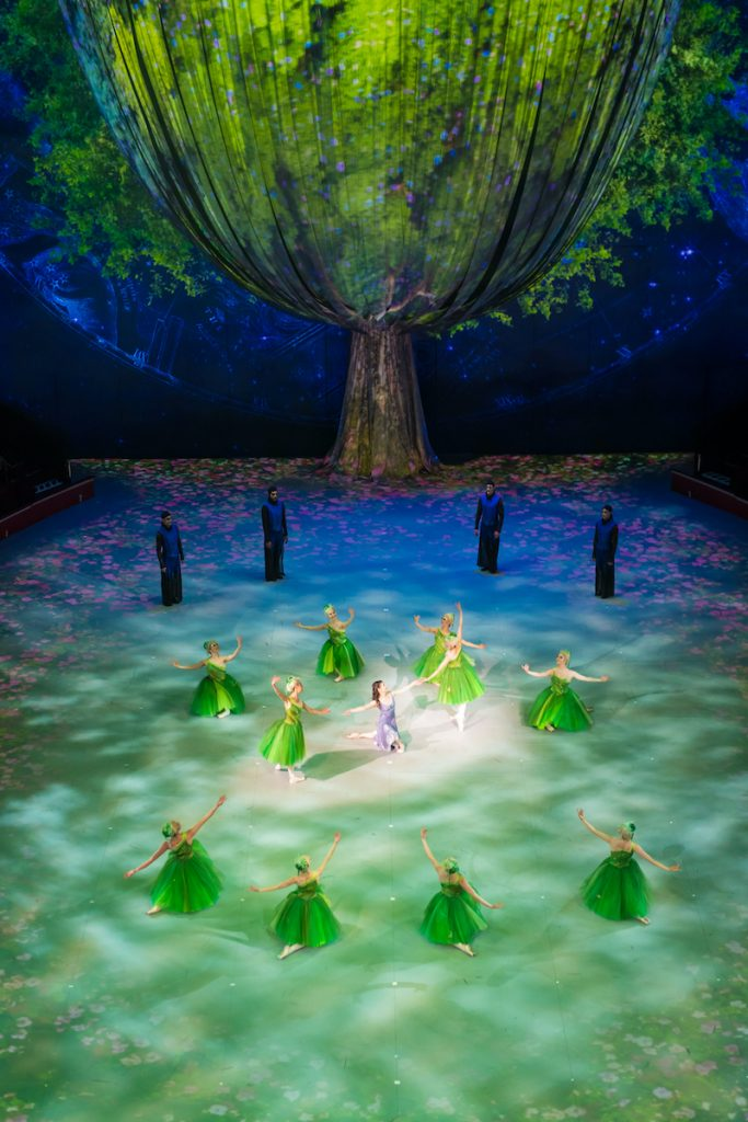 A circle of dancers stand on stage under green light and a tree projection