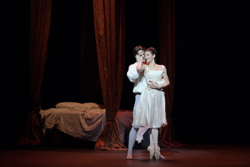 A man embraces a ballerina en pointe on stage