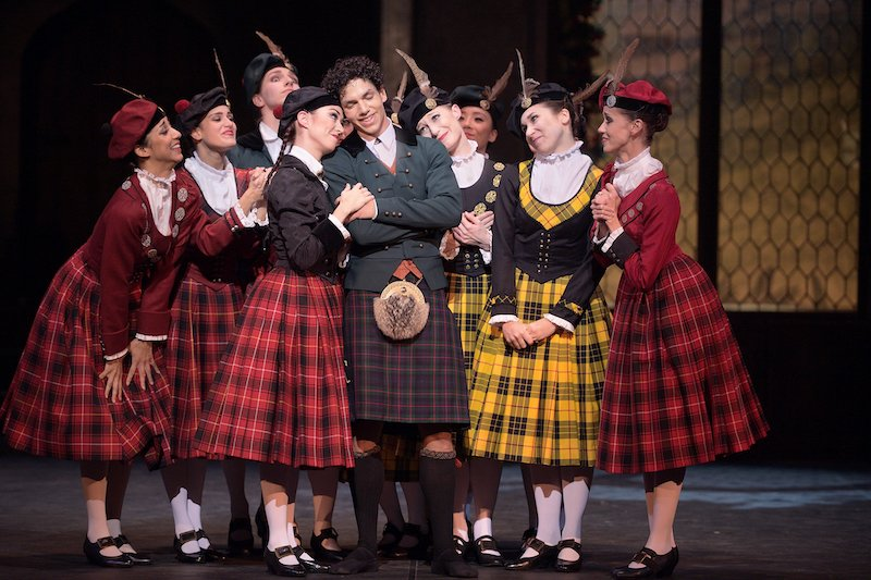 A group of women in kilt-like skirts surround a happy couple