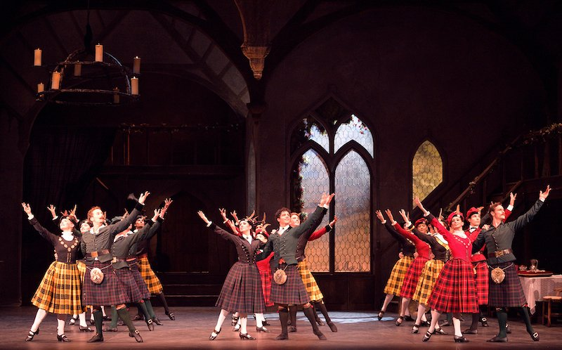 Dancers in kilts raise their arms towards the ceiling