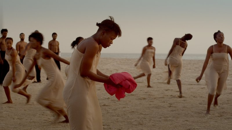 A woman holds a pink cloth as others run behind her on the beach