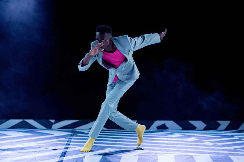 A man in a suit and bright yellow socks leans tilts his torso forward on stage
