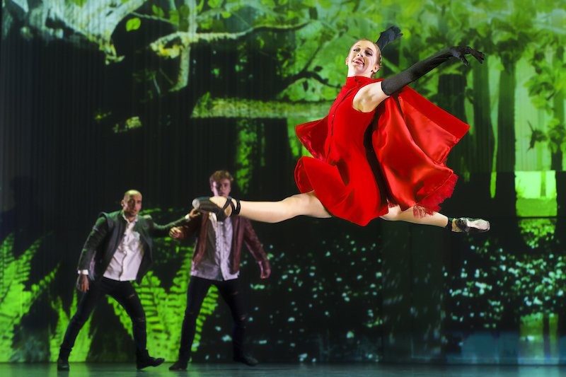 A ballerina with a red cape leaps through the air.
