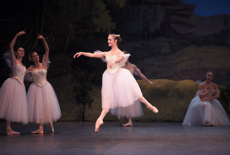A woman in a tutu lightly leaps into the air