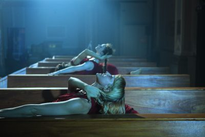 Two female dancers in red lean back in between wooden church pews