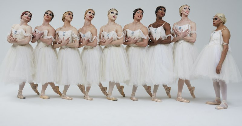Men stand in a row, wearing tutus and pointe shoes