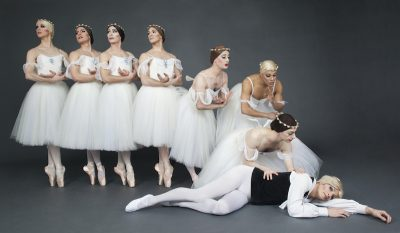 Men in tutu and pointe shoes checks a man on the floor