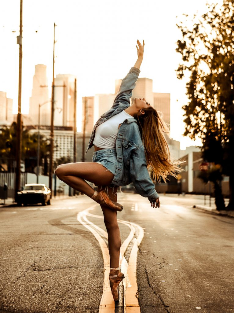 A woman raises on arm and leans back as she stands on one leg in pointe shoes