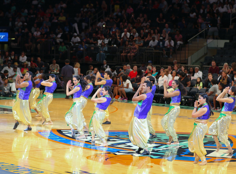 Bollywood dancers perform on a basketball court