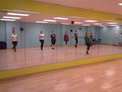 Women learning Irish dance stand in front of a mirror