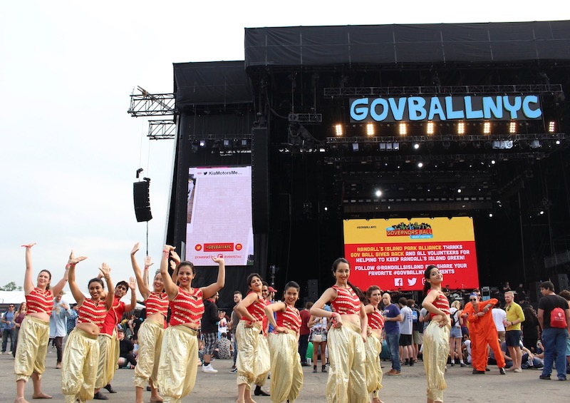 Bollywood dancers in bright orange tops and gold pants pose in front of an outdoor stage